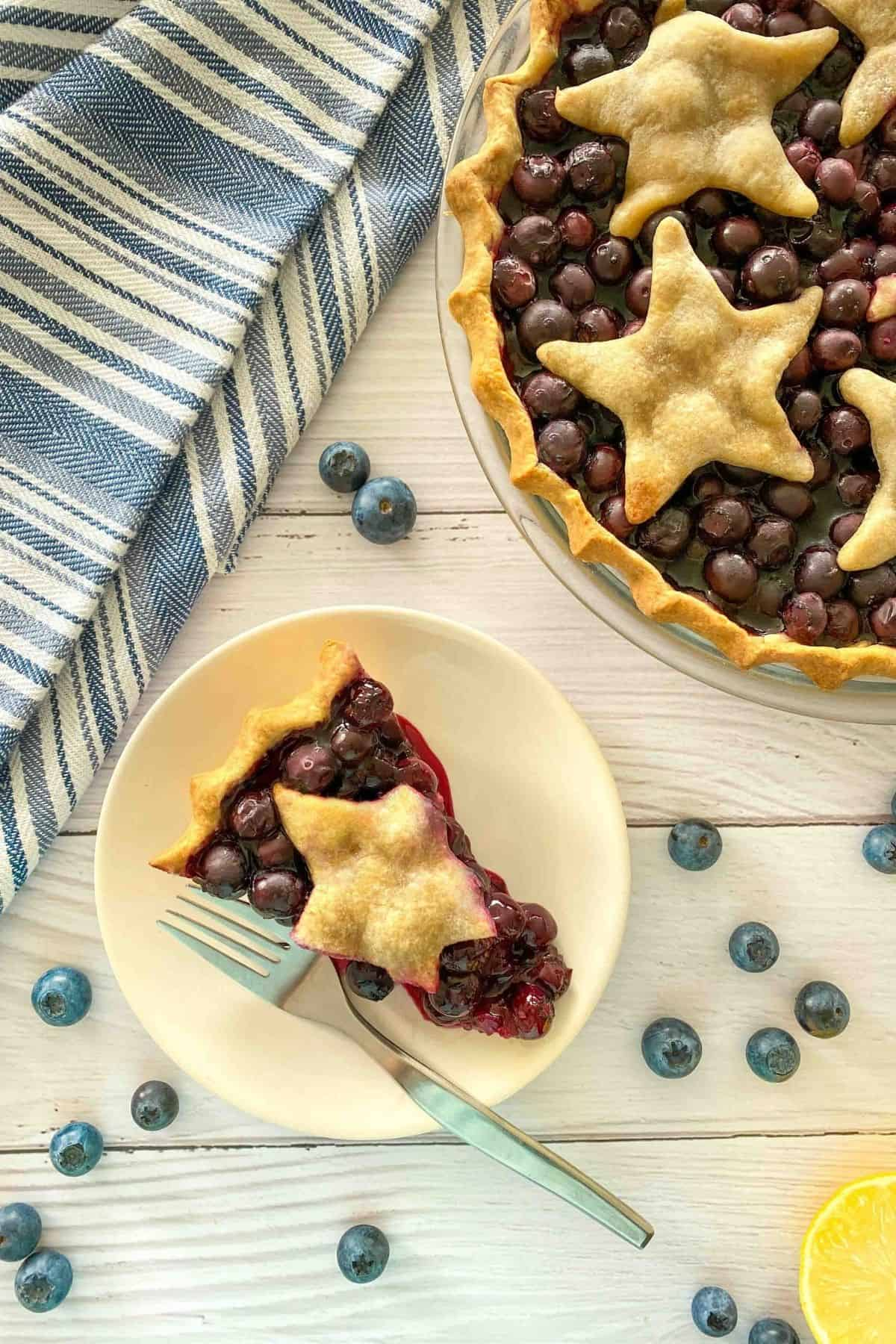 Slice of blueberry pie on white dish with fork with remaining pie in background.