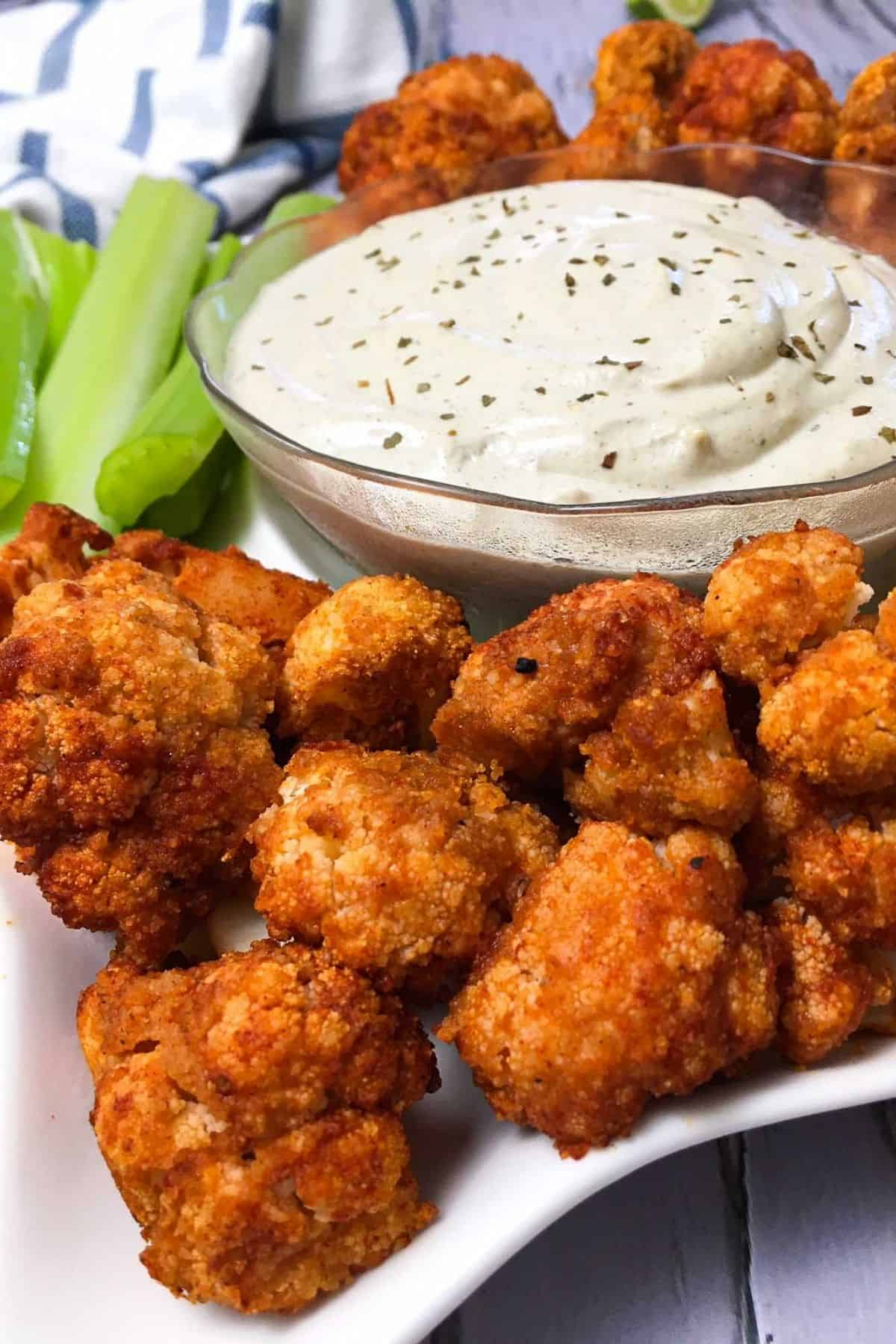 Tray of buffalo cauliflower bites with bowl of ranch dip in the middle.