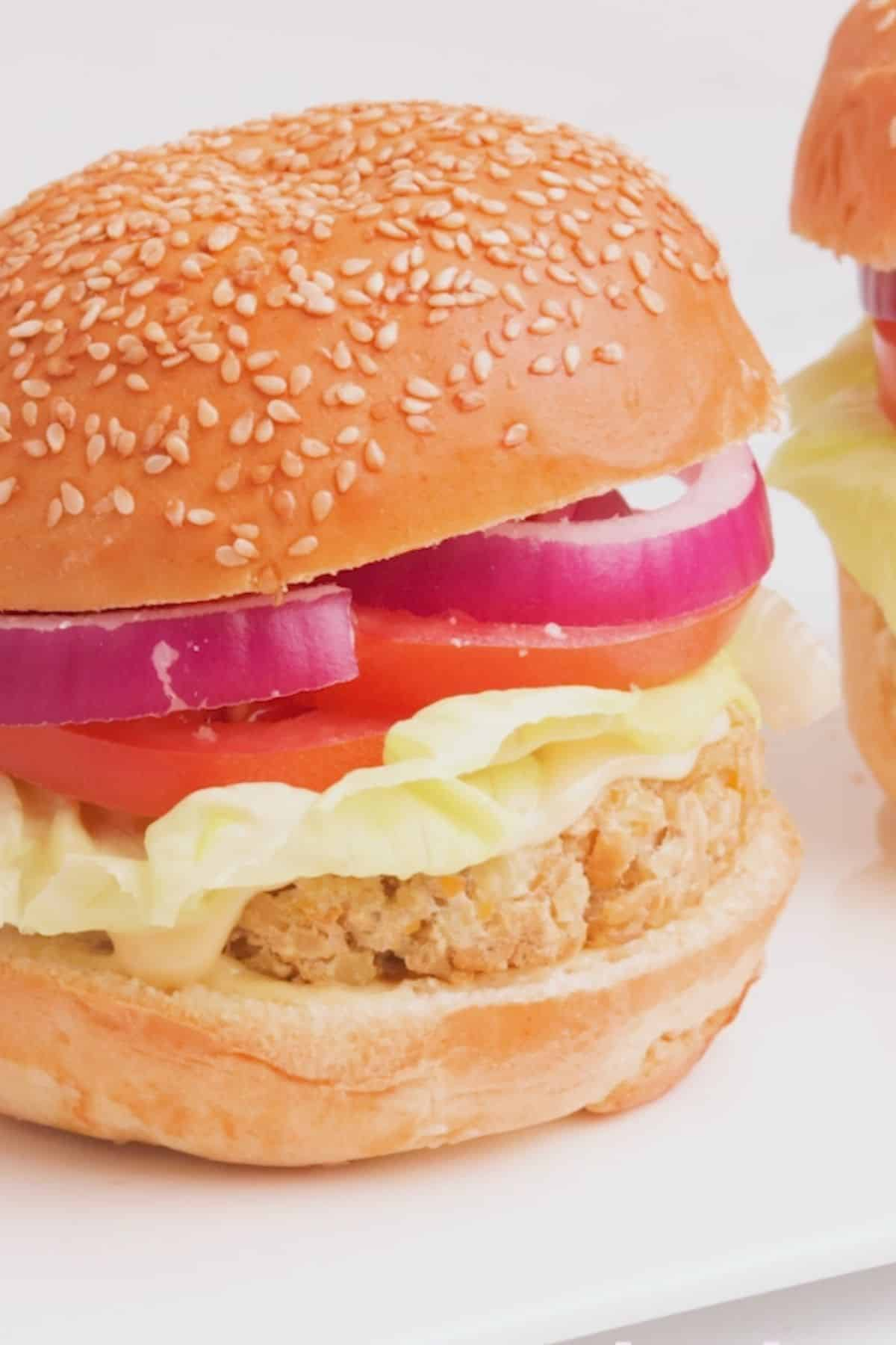 Vegan chicken burger in bun with onion, tomato, lettuce and mayo.
