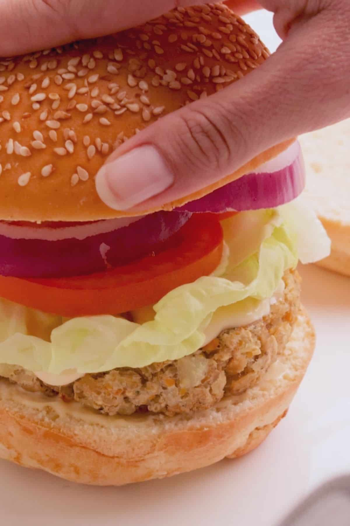 Hand placing top bun over burger and toppings.