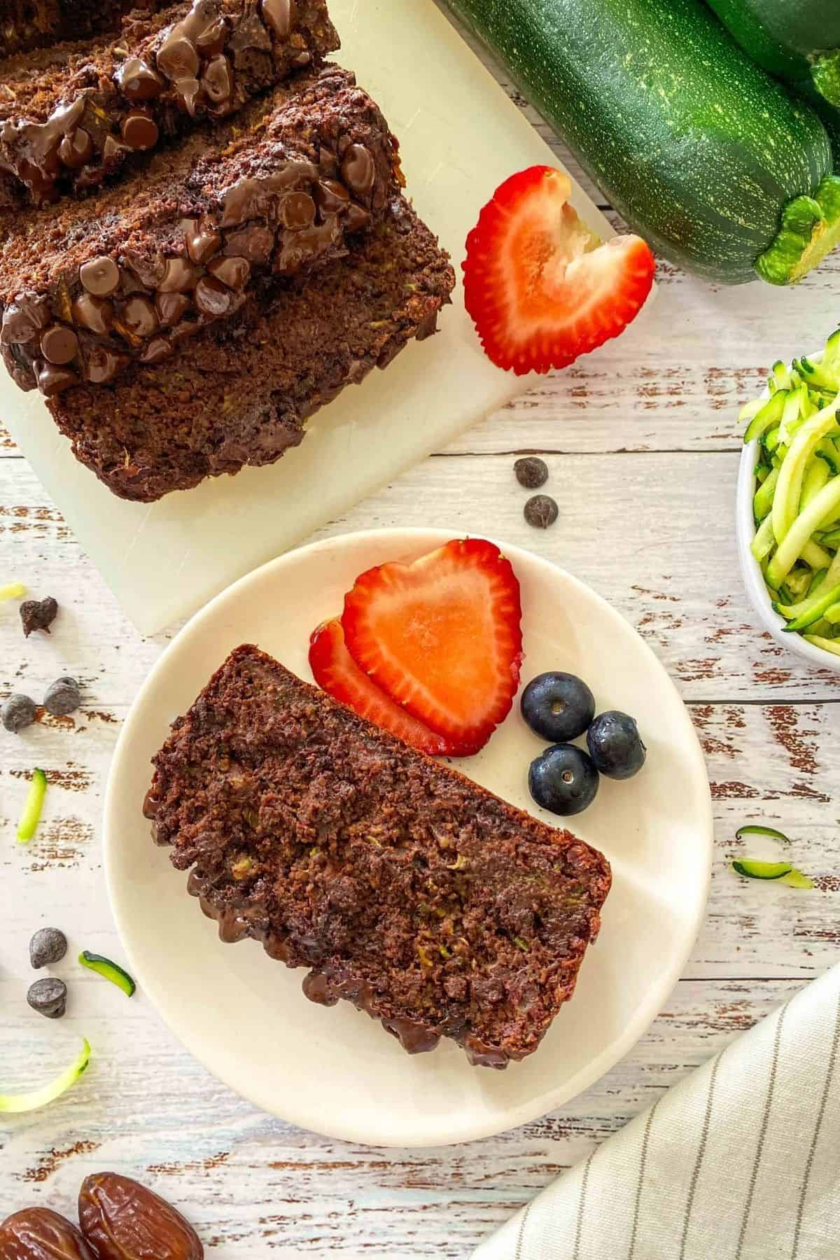 Sliced chocolate zucchini bread on cutting board with one slice on plate with strawberries and blueberries.