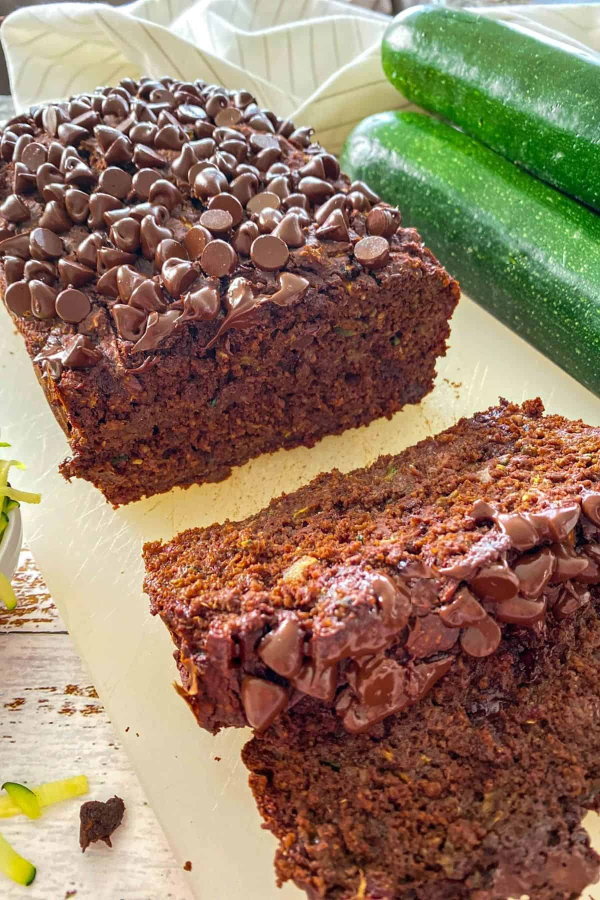 Loaf of chocolate zucchini bread on cutting board with two slices in front on their side.