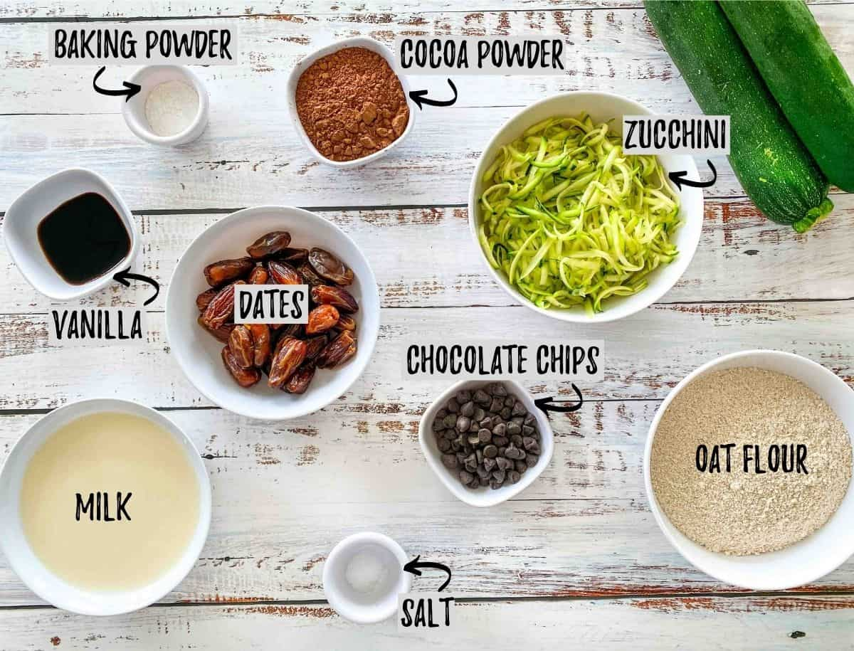 Ingredients needed to make vegan chocolate zucchini bread scattered on deck.