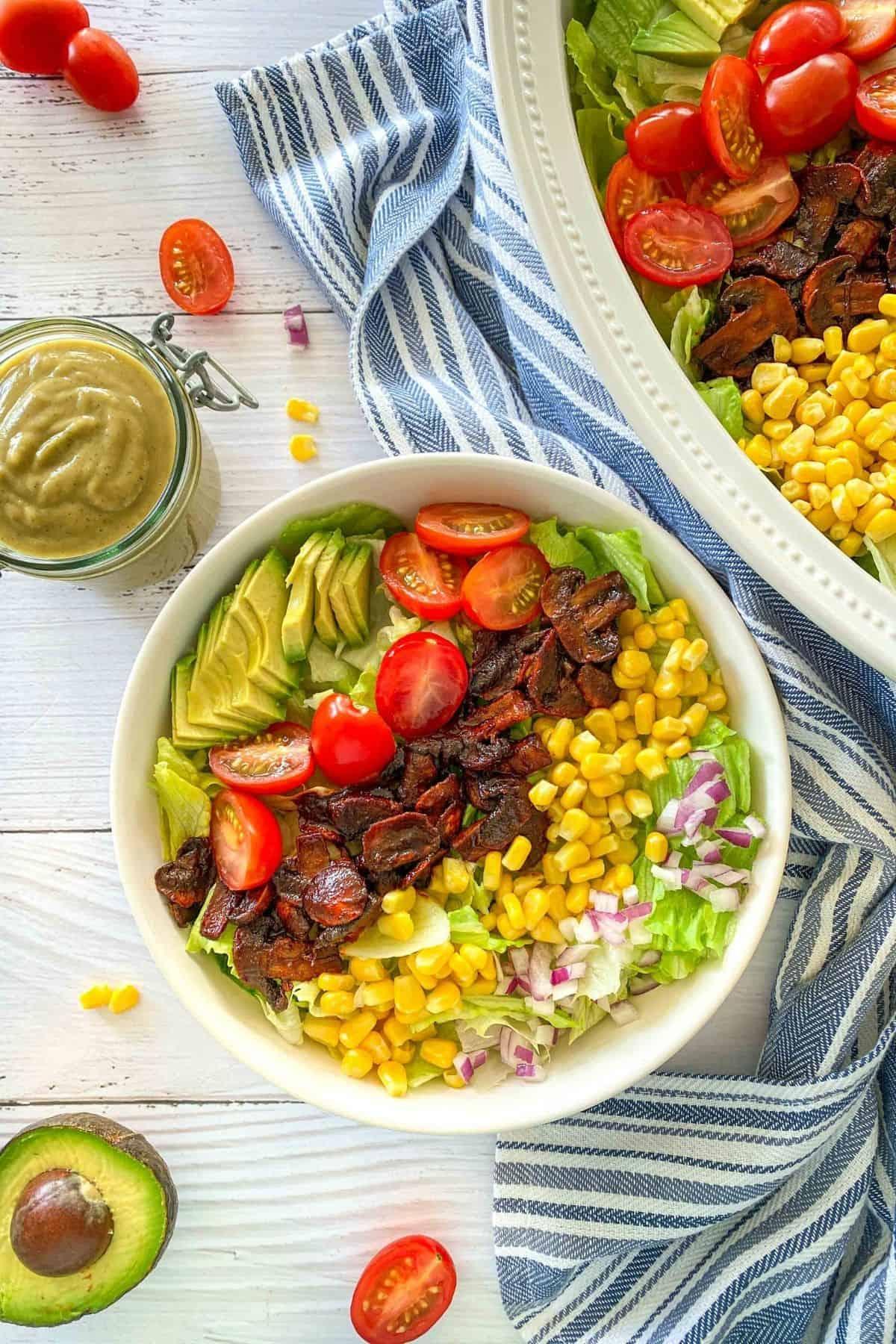 Vegan cobb salad in white bowl with jar of dressing behind it.