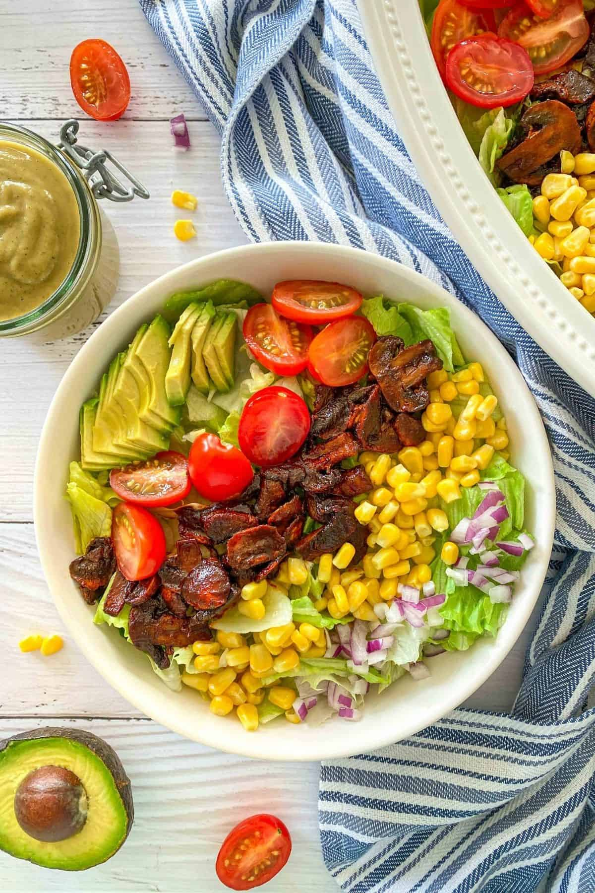 Lettuce, avocado slices, halved grape tomatoes, cooked mushrooms, corn kernels and red onion in white bowl.