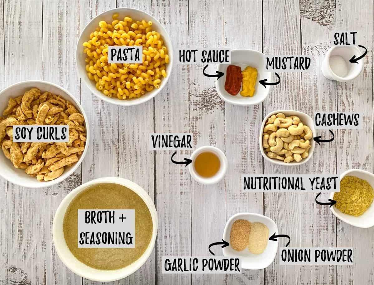 Ingredients scattered on grey deck to make vegan pasta dish.