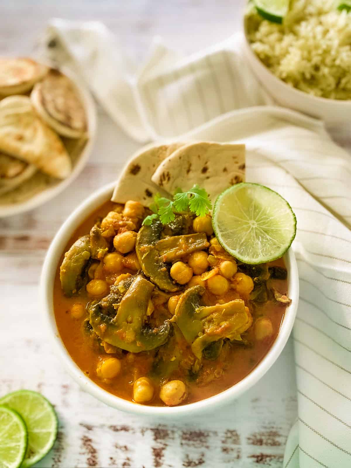 white bowl with vegan curry and lime and naan wedges on top