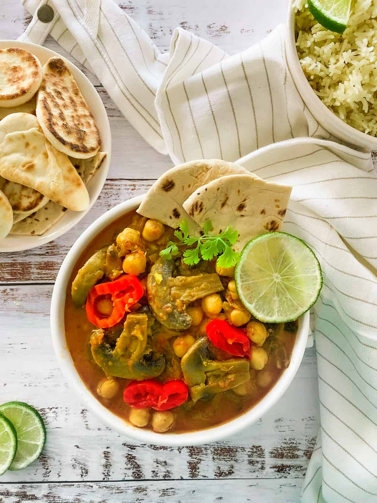 white bowl of chickpea mushroom curry with naan bread and lime garnish