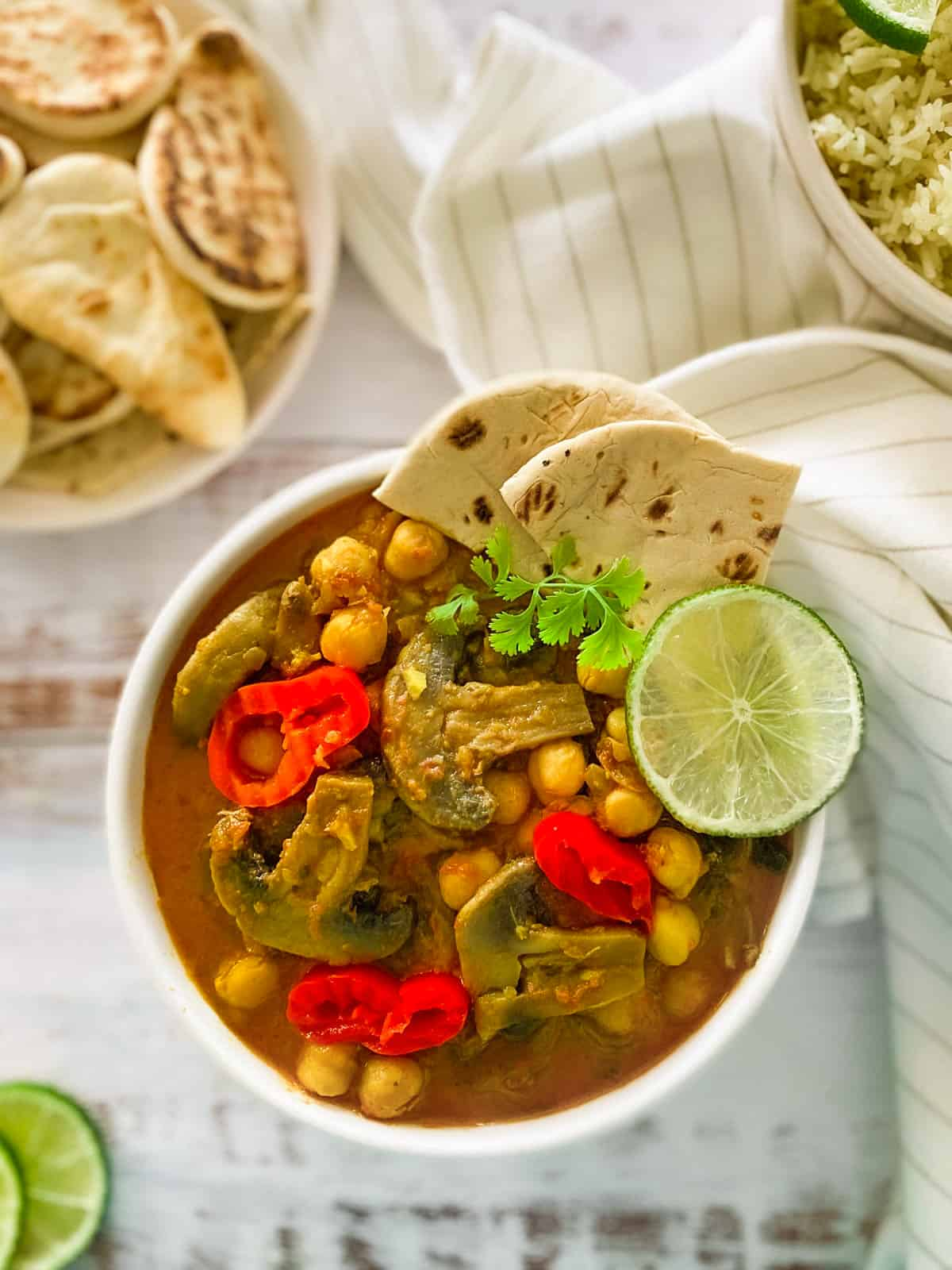 white bowl of mushroom and chickpea curry with red chilies garnished on top and naan bread on the side