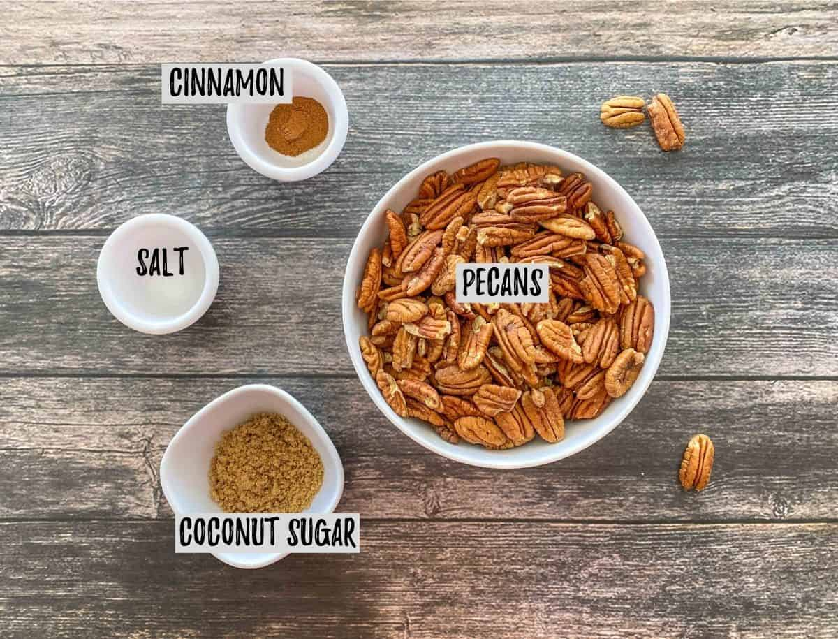 Bowl of pecans with small prep bowls of salt, cinnamon and sugar around it.