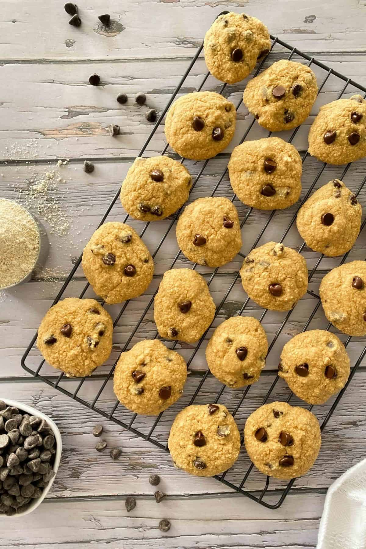 Chocolate chip cookies on wire rack with cup of flour and bowl of chocolate chips on the side.
