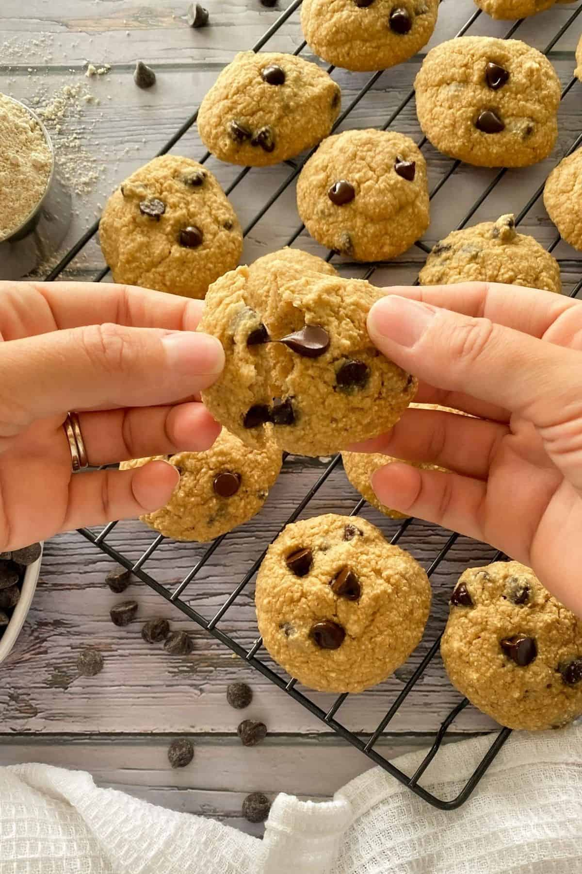 Hand pulling apart chocolate chip cookie into two halves.