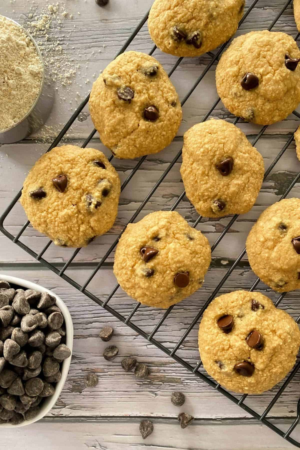 Cookies on cooling rack with cup of flour and chocolate chips on the side.