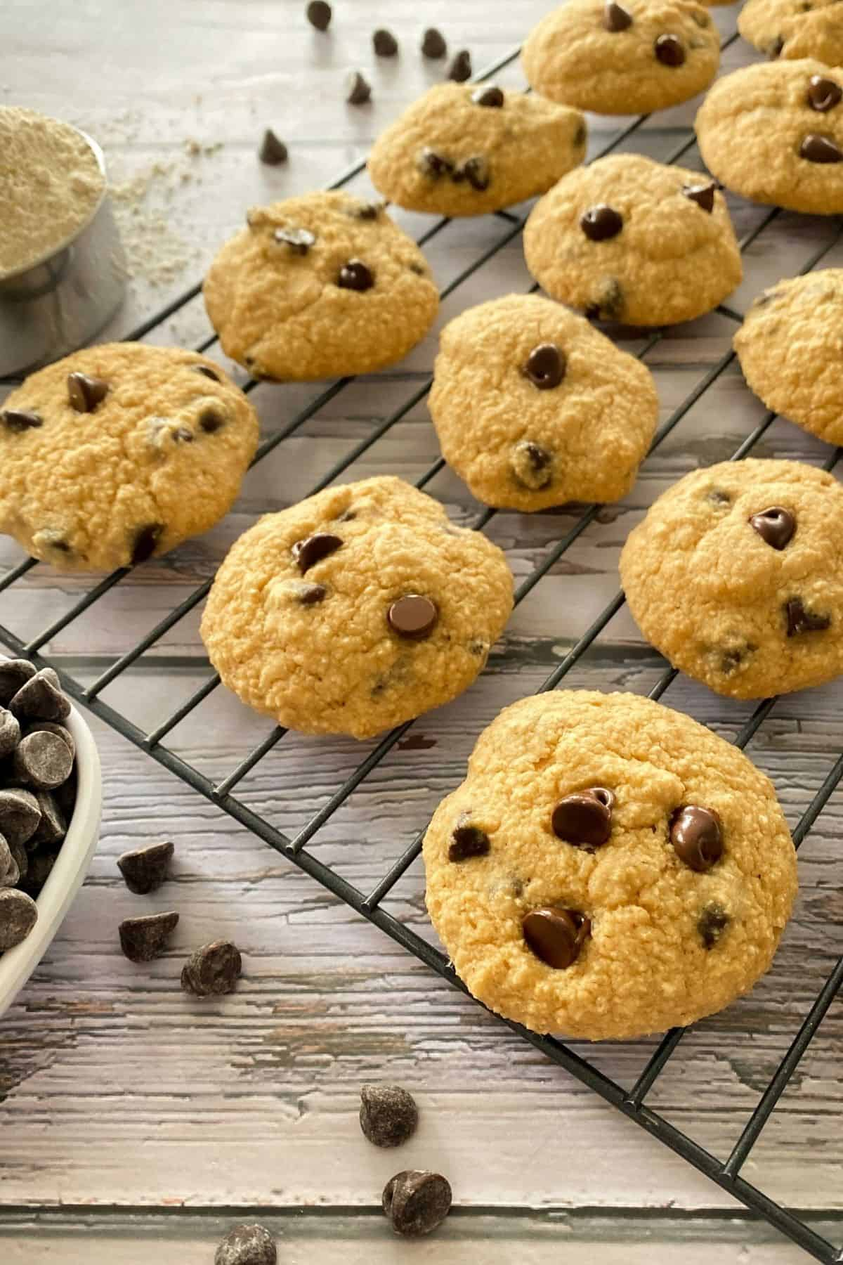Chocolate chip cookies on cooling rack with chocolate chips on the side.
