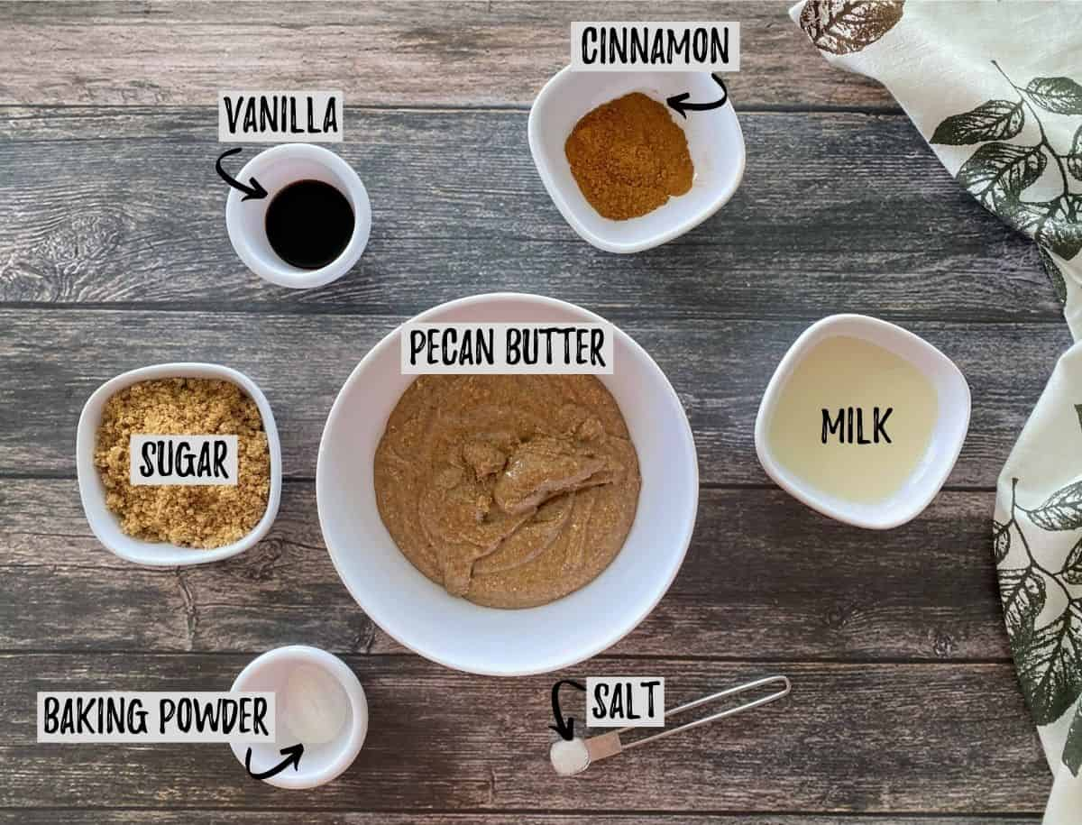 Ingredients to make pecan butter cookies scattered on brown deck.