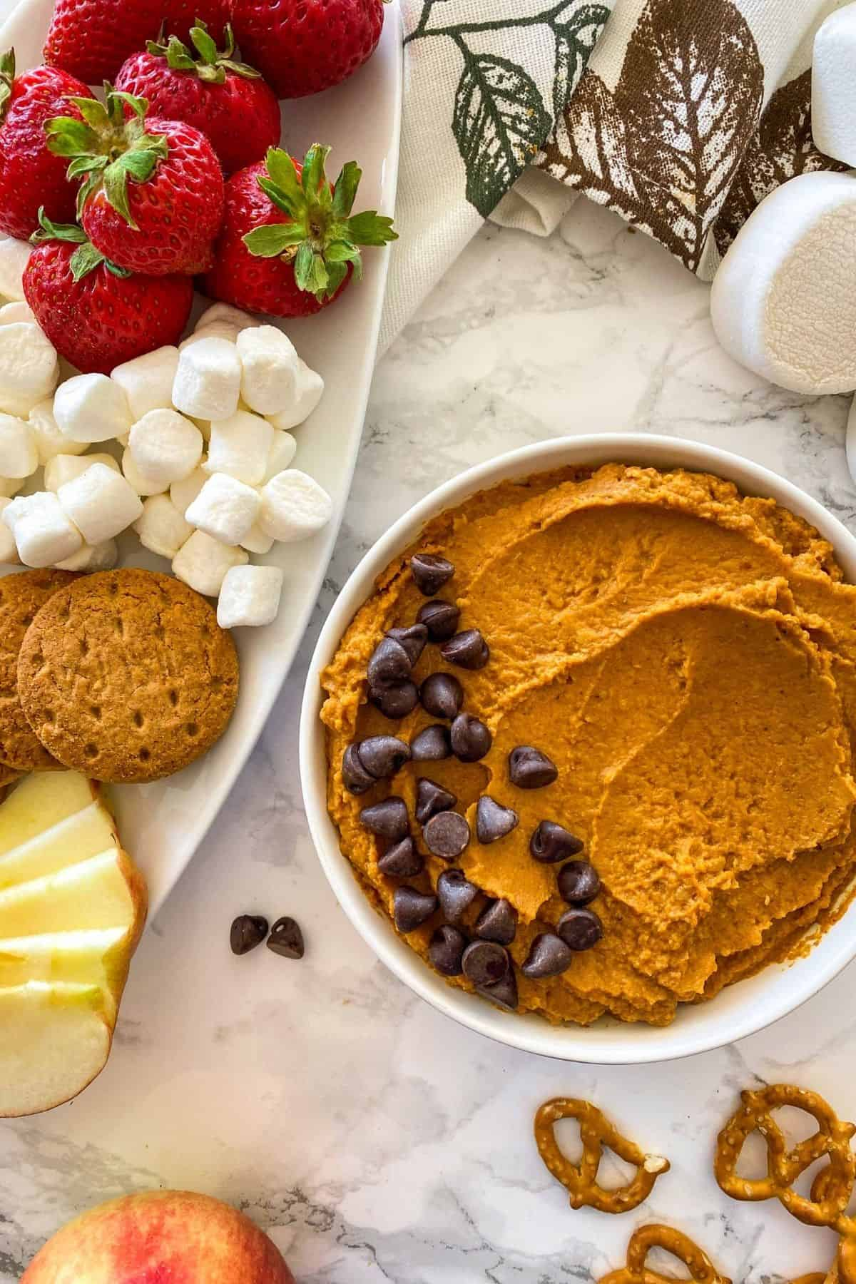 Bowl with orange dip inside and chocolate chips on top.