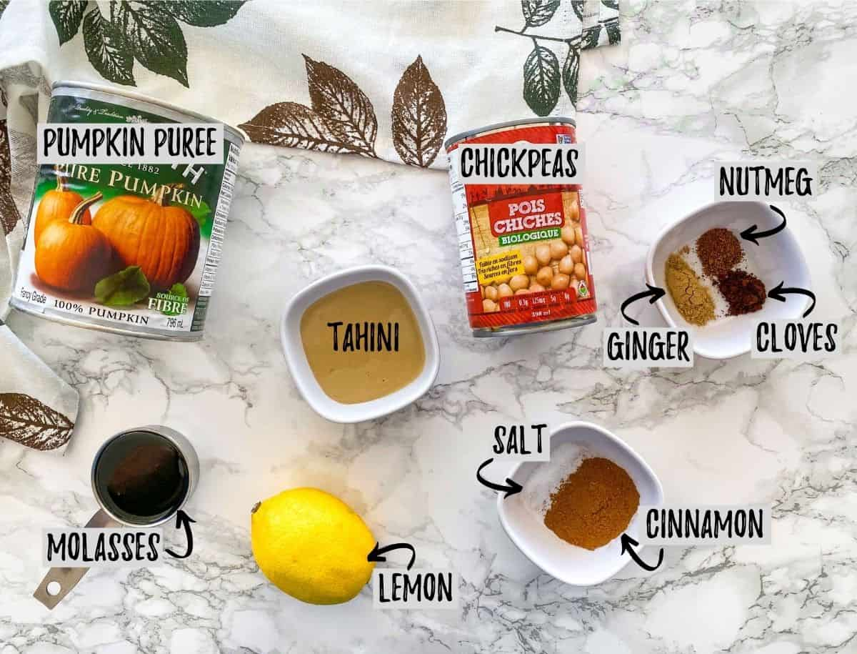 Ingredients needed to make pumpkin spice hummus scattered on marble counter.