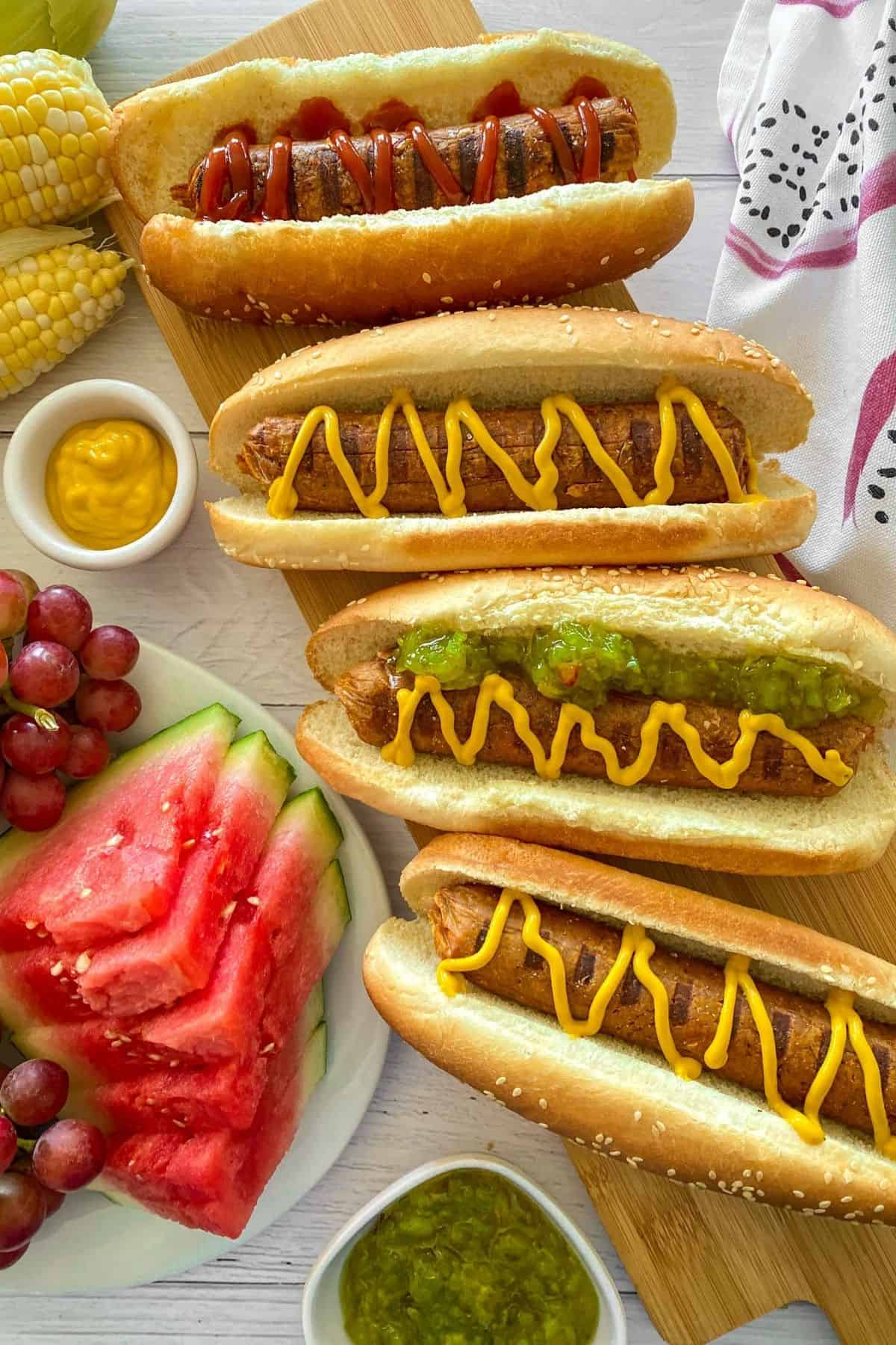 Vegan hot dogs in buns with mustard and relish on top.