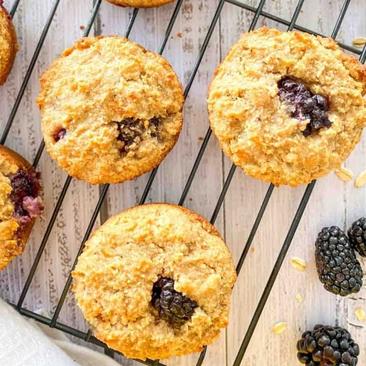 Cooling rack with blackberry muffins on top.
