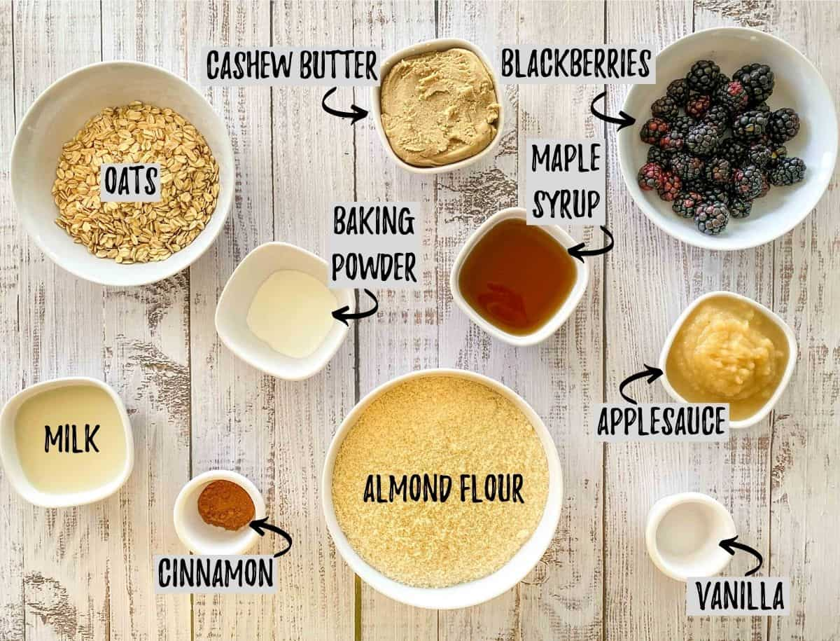 Ingredients to make muffins scattered in prep bowls on grey deck.