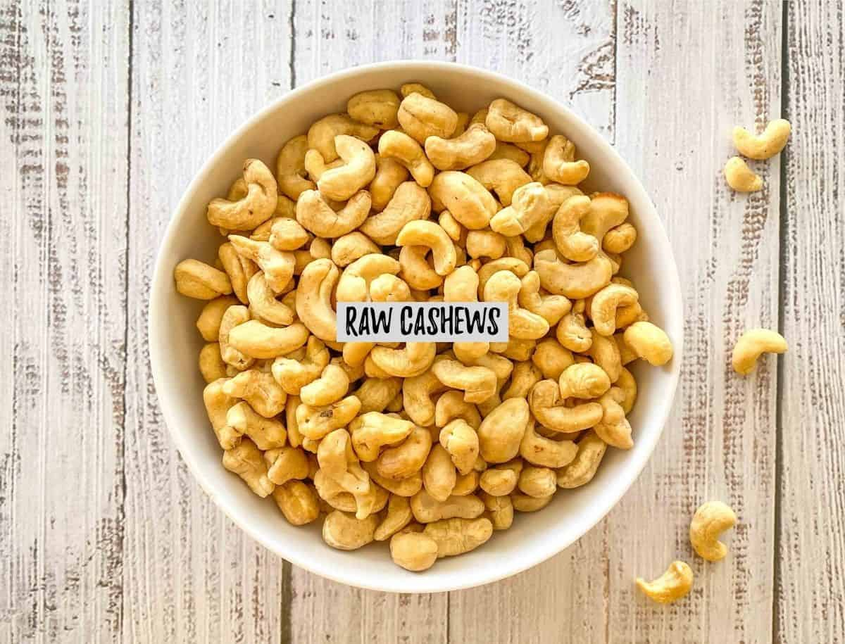 White bowl filled with raw cashews and some scattered around the bowl.