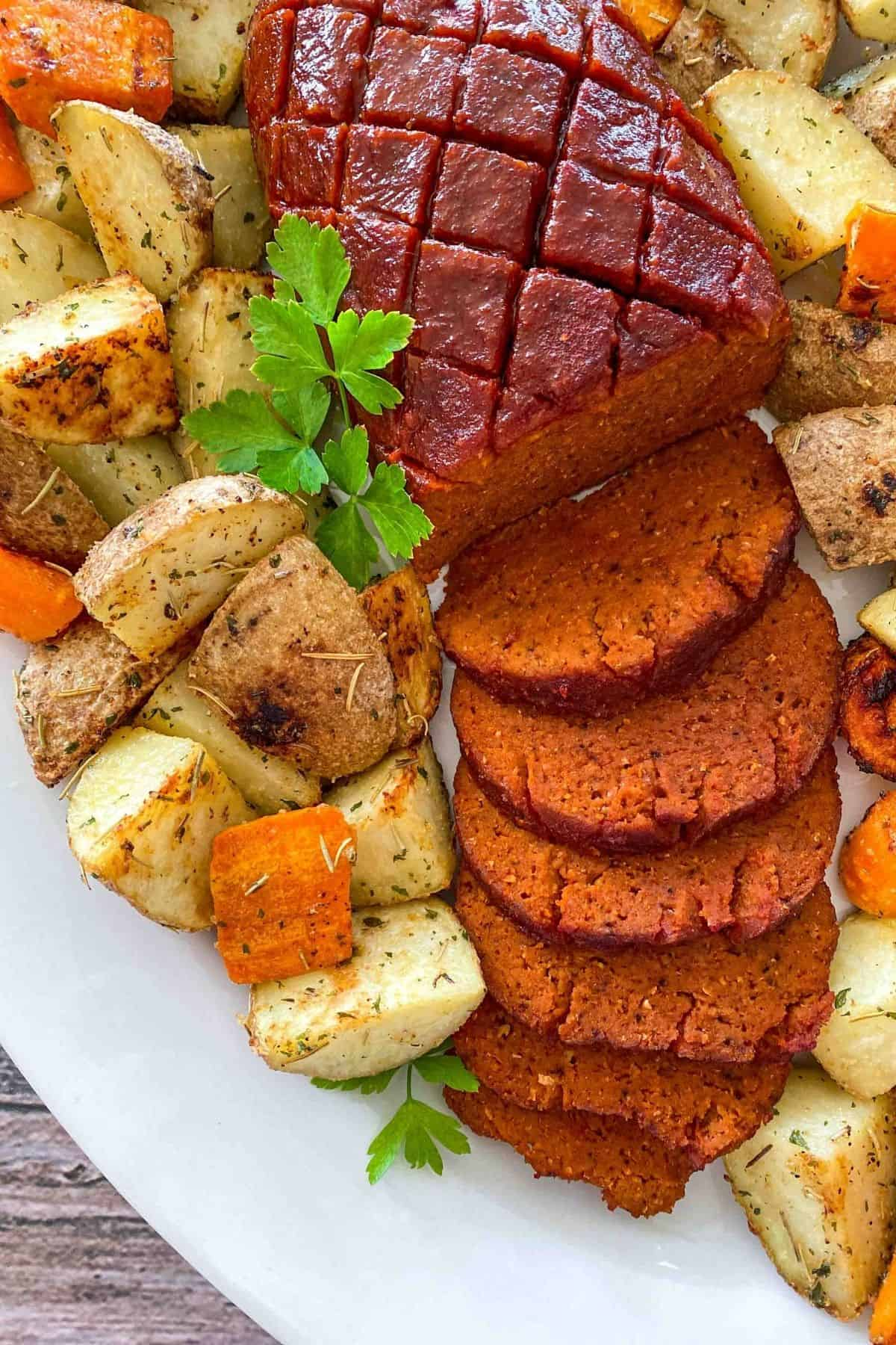 Platter with sliced vegan ham and roasted potatoes and carrots around it, with parsley garnish.