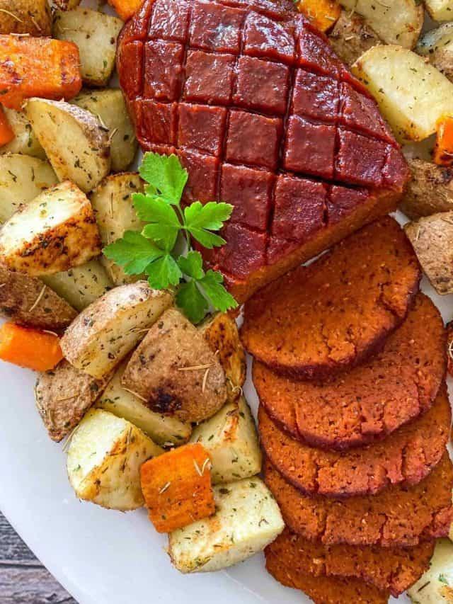 Vegan ham roast on platter with roasted carrots and potatoes around it.