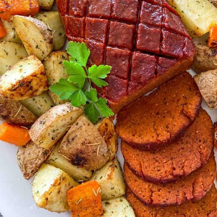 Vegan ham sliced on platter with roasted potatoes around it.