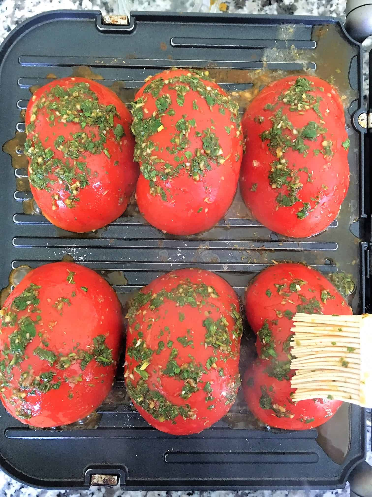 Halved tomatoes on grill being brushed with chimichurri sauce.
