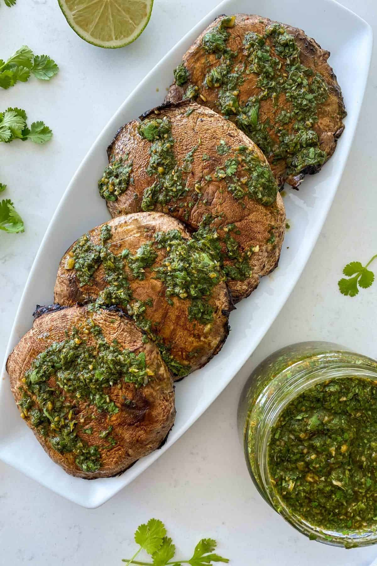 Platter of grilled portobello mushrooms with chimichurri sauce on top and jar of chimichurri beside it.
