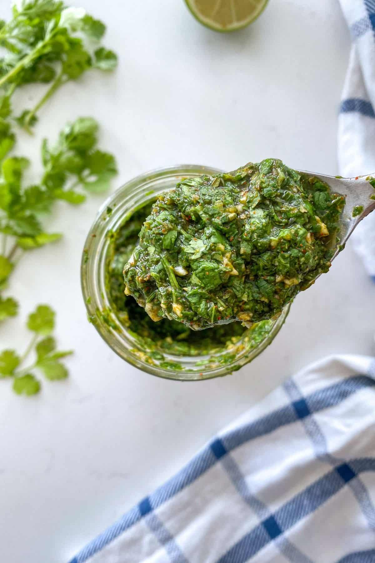 Spoonful of chimichurri being scooped from glass jar with herbs and lime in the background.