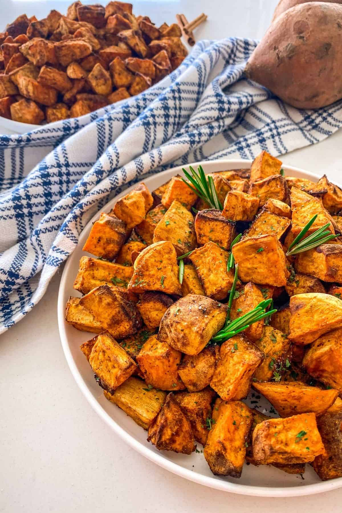 Side angle of cooked sweet potatoes in white plate with rosemary garnish and blue towel behind it.