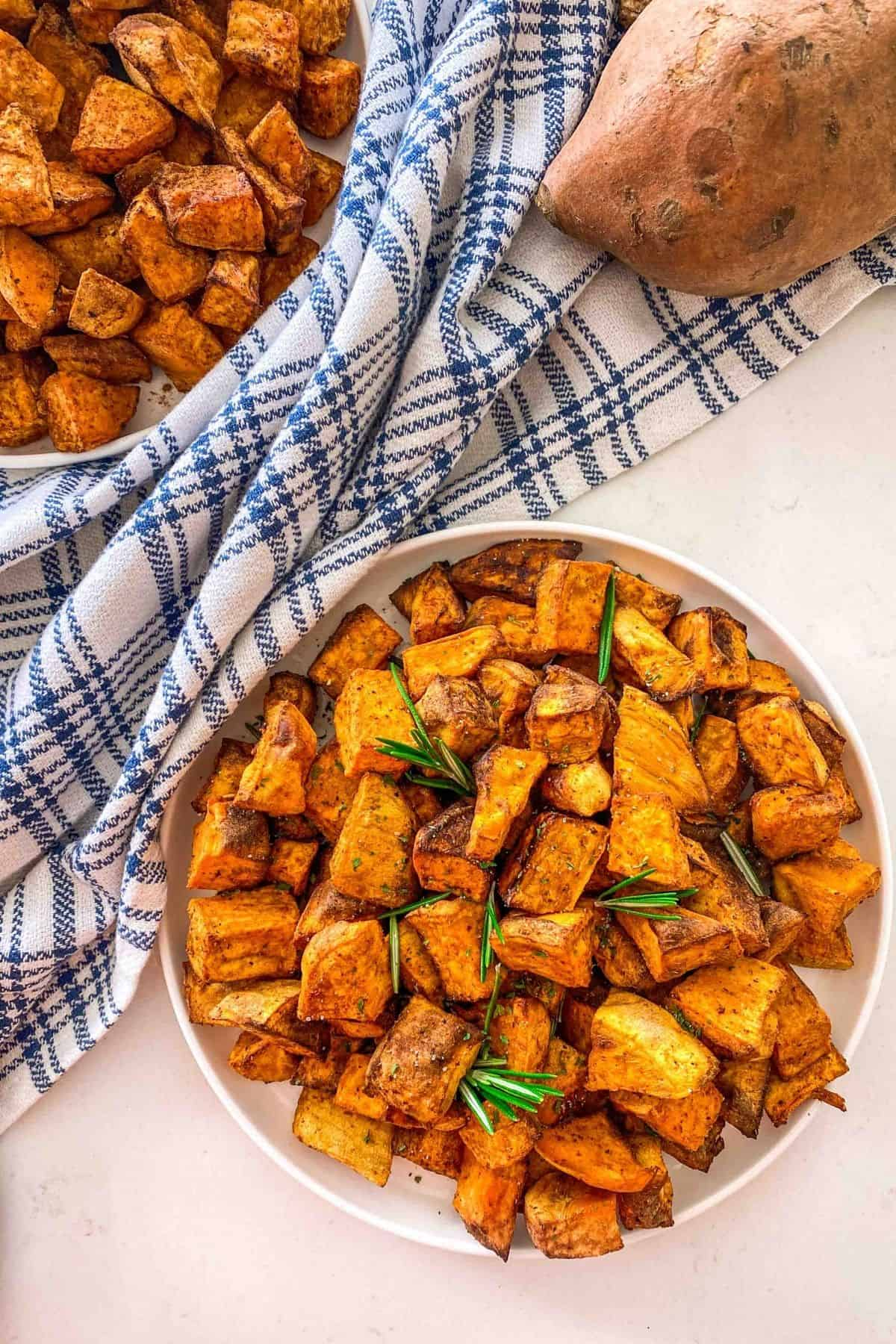 Two plates of sweet potato cubes with rosemary garnish.