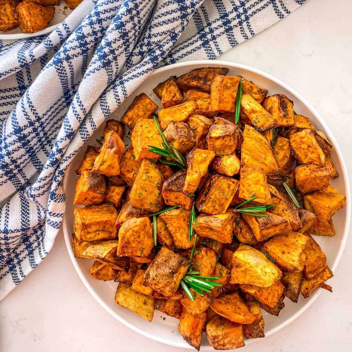 White plate with cubed sweet potatoes and rosemary garnish.