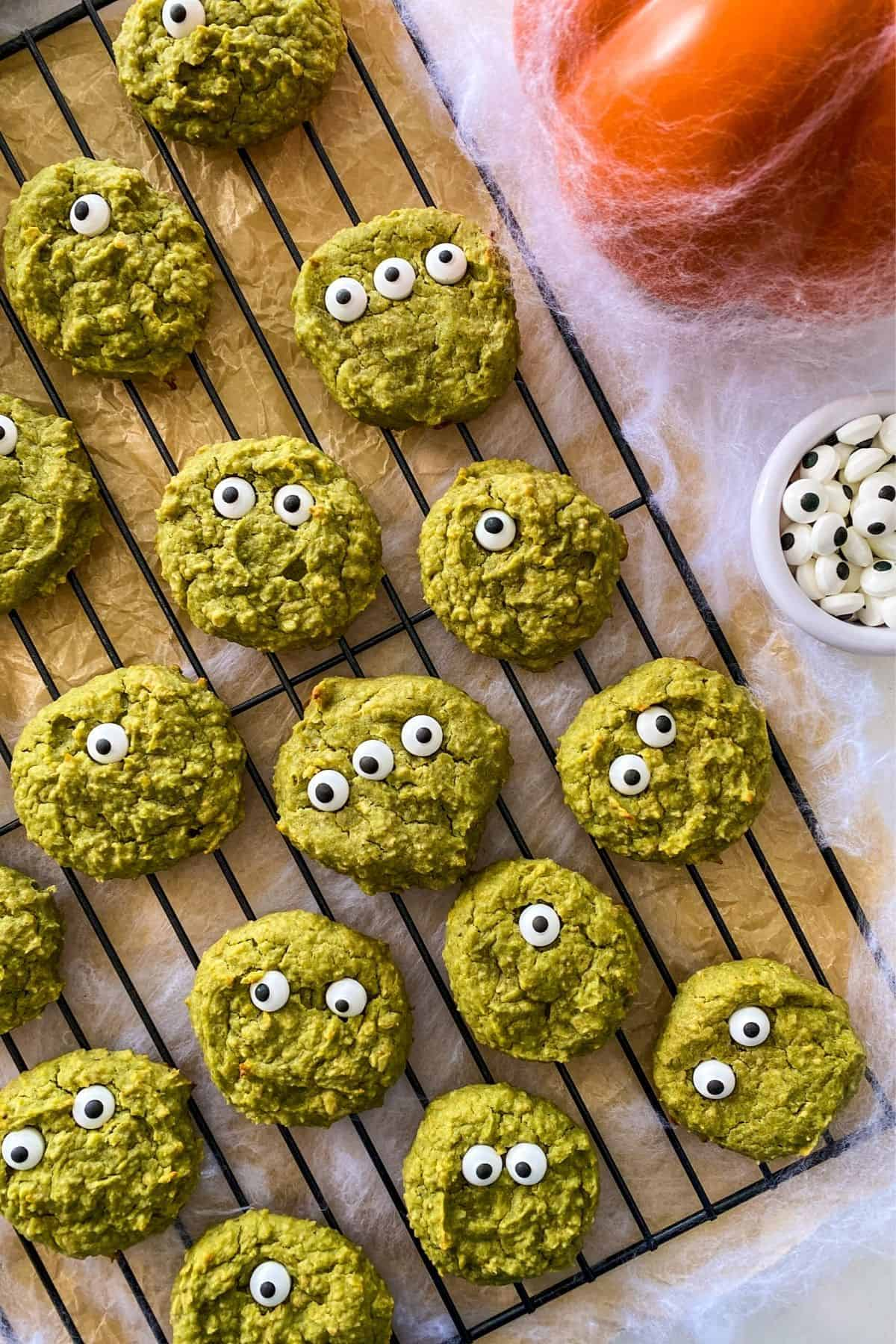 Green cookies with candy eyes on cooling rack with cobwebs around it.