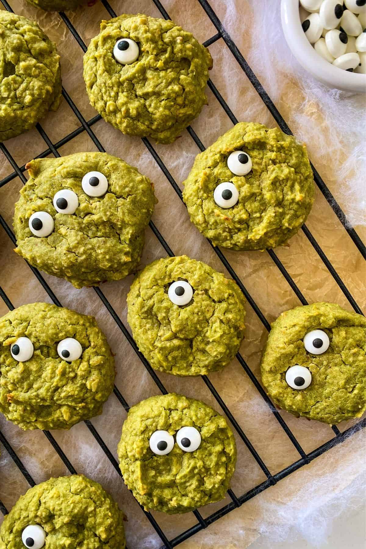 Green cookies with candy eyes on cooling rack.