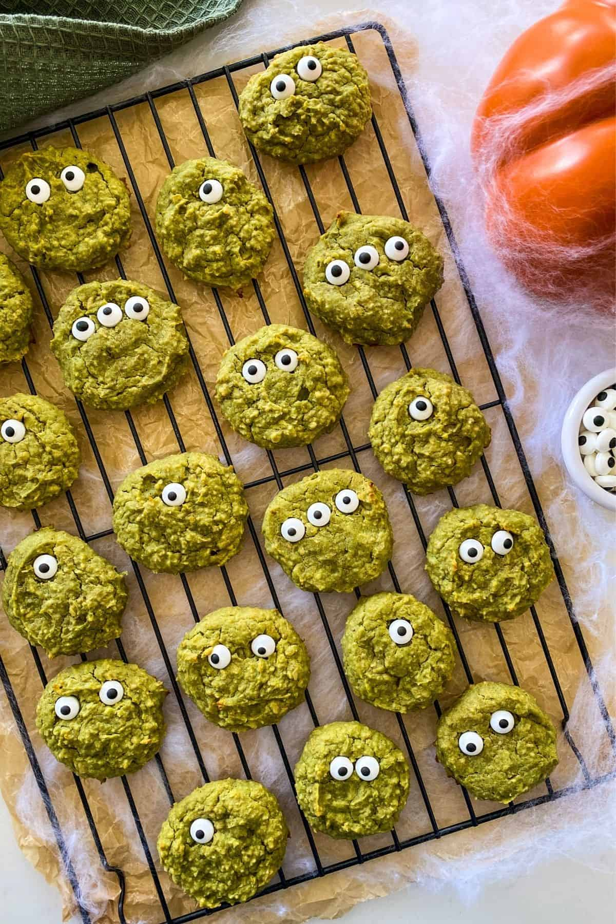 Green cookies on cooling rack with pumpkin and bowl of candy eyes beside them.