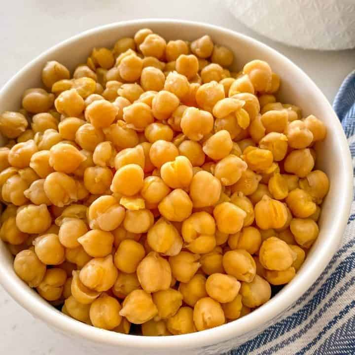 White bowl filled with cooked chickpeas and blue towel beside it.