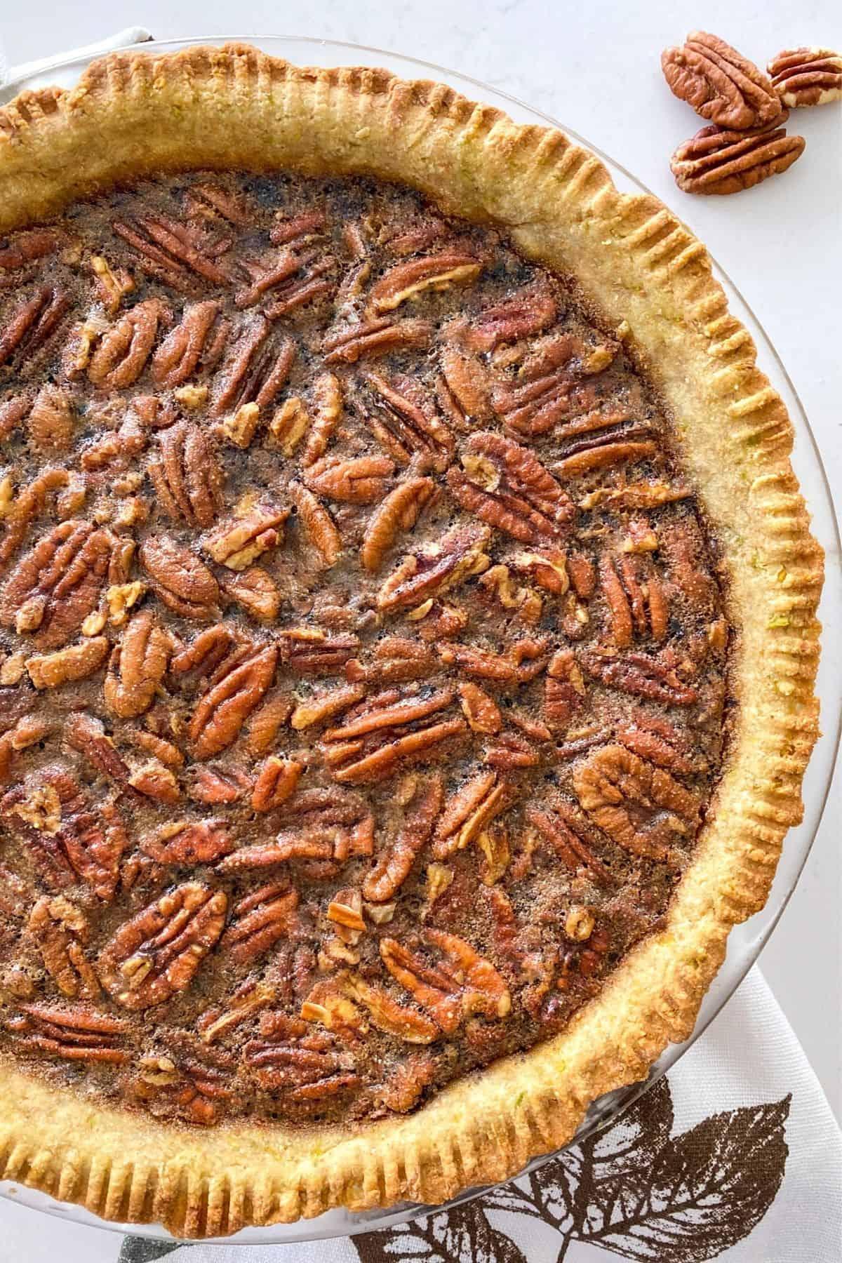 Close up of vegan pecan pie in pie plate.