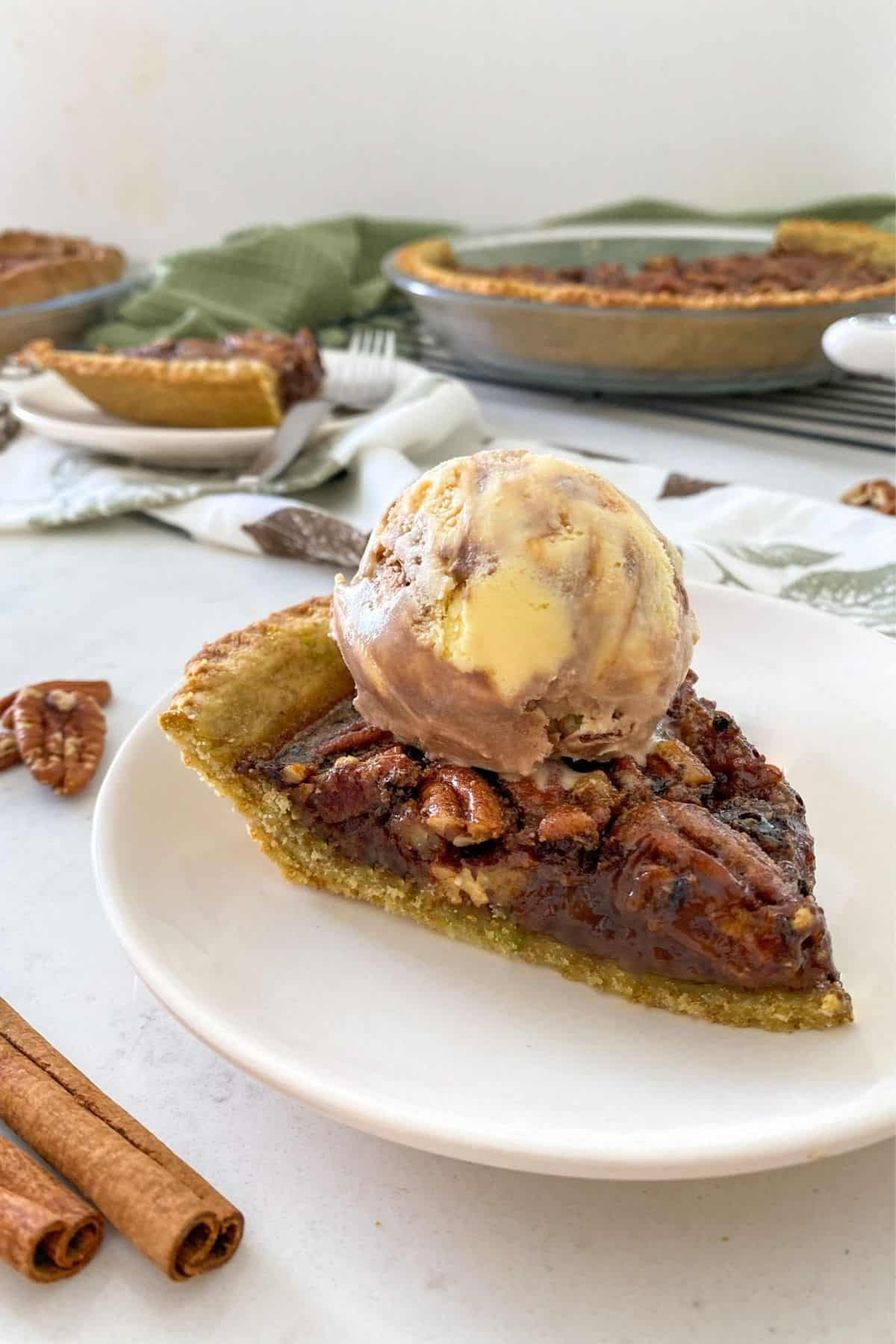 Slice of pecan pie on plate with scoop of ice cream on top.