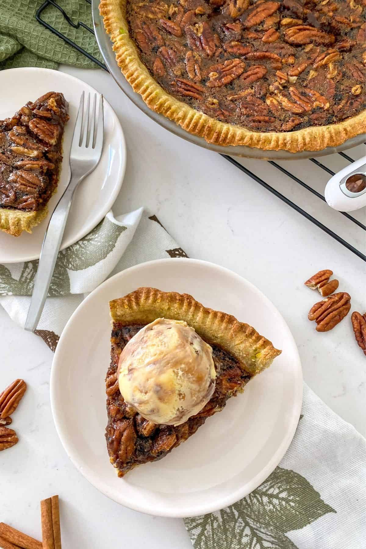 Pecan pie in pie plate with two slices of pie in small dessert plates and scoop of ice cream on top.