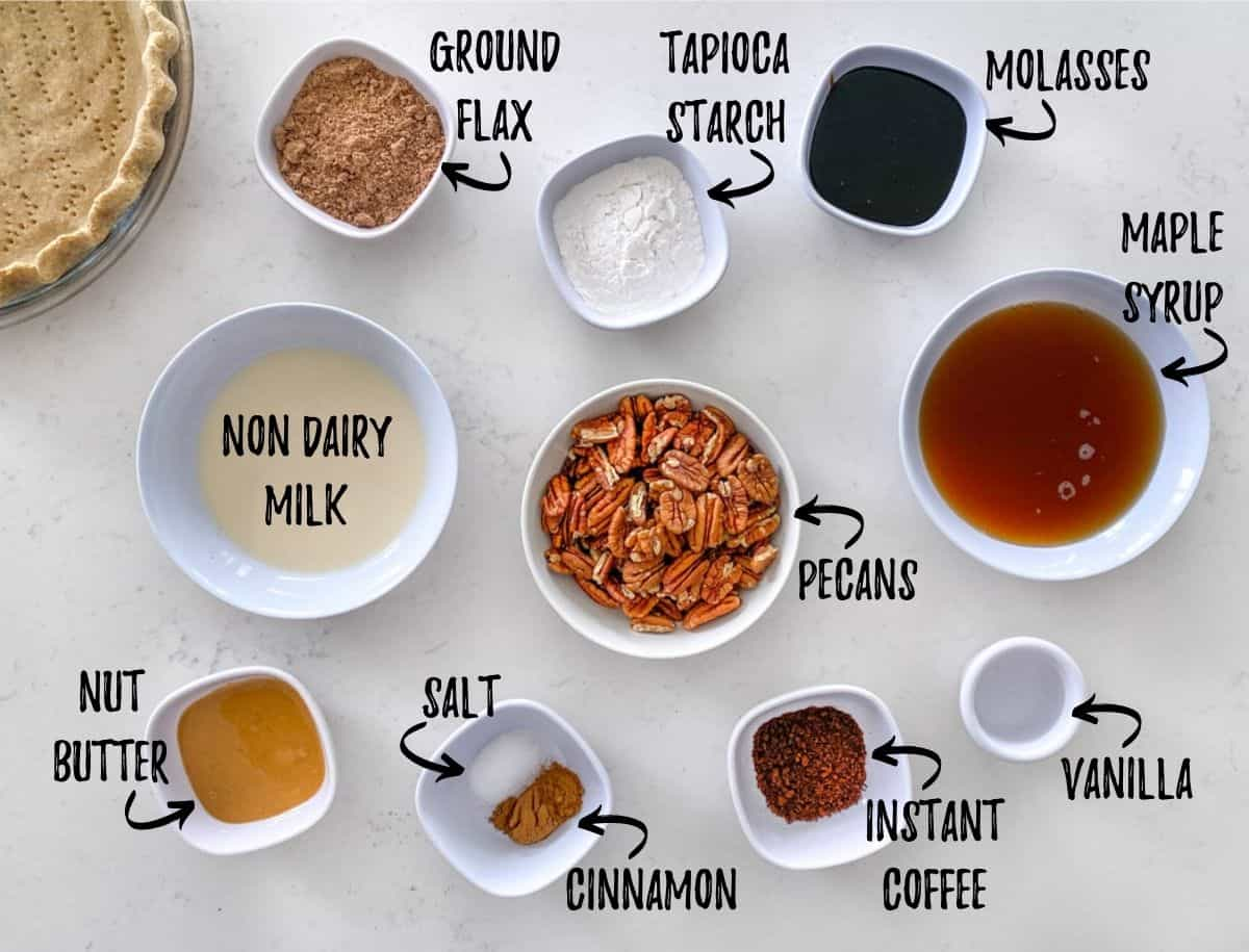 Ingredients to make pecan pie in prep bowls scattered on counter top.