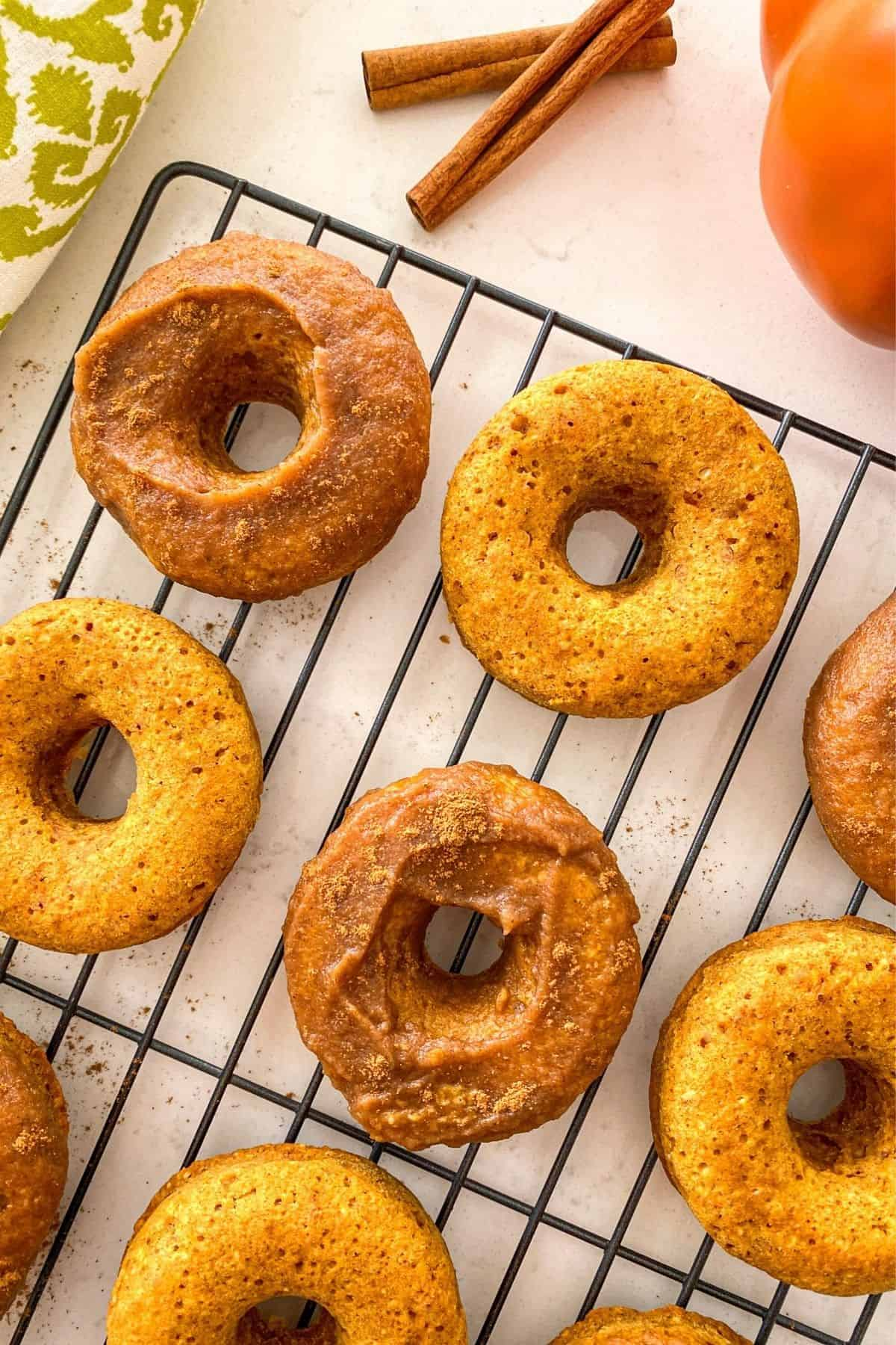 Pumpkin donuts on cooling rack with half plain and half glazed.