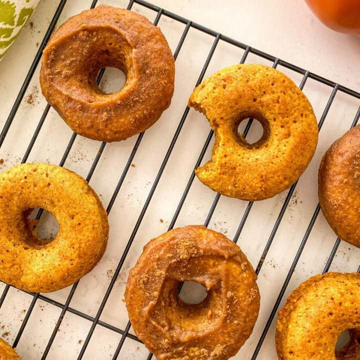 Pumpkin donuts on cooling rack with bite taken out of one of them.