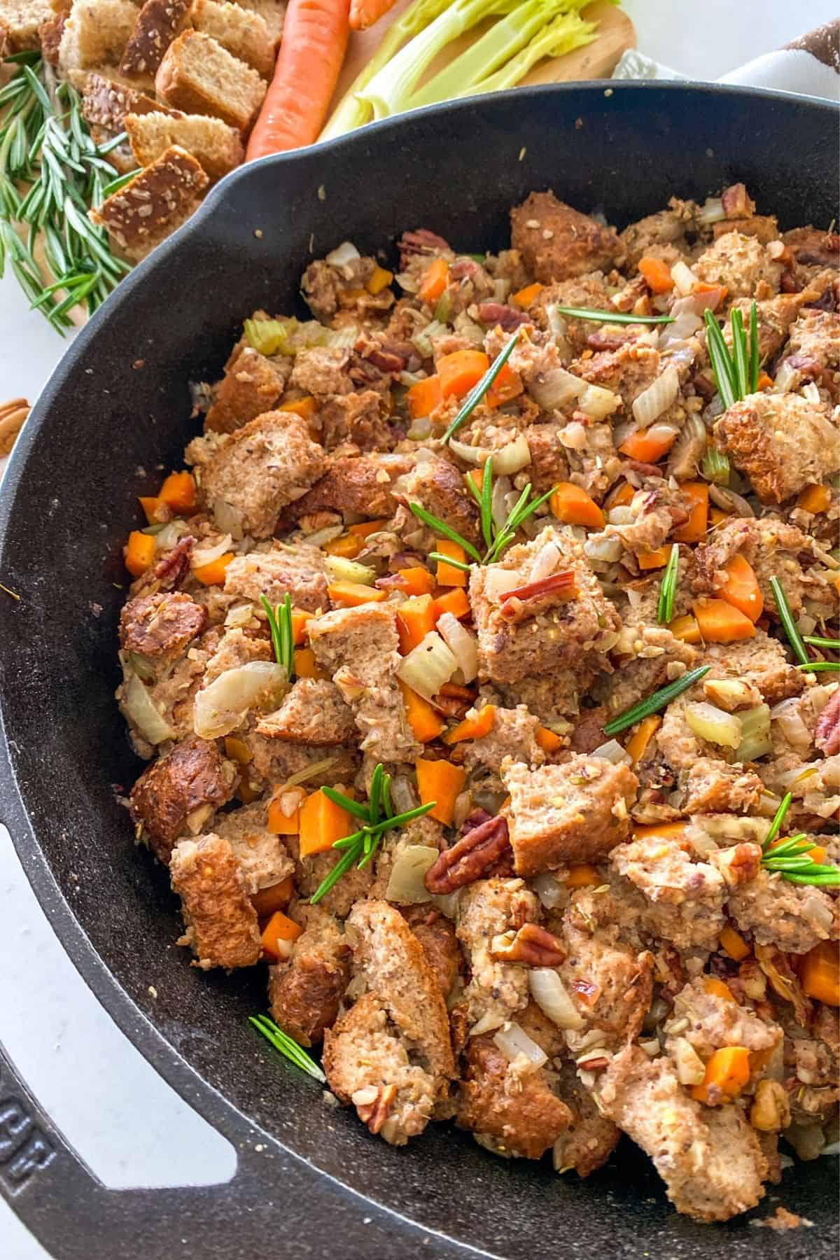 Vegan stuffing with bread, chopped veggies and fresh rosemary in cast iron pan.