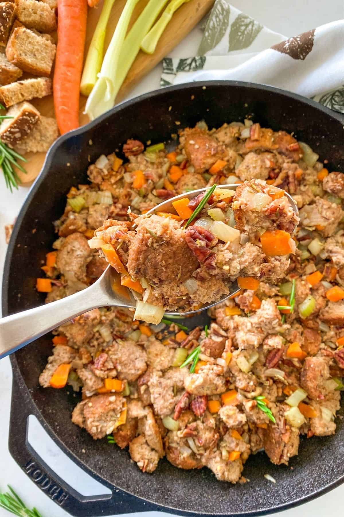 Spoonful of vegan stuffing being held up above cast iron pan with remaining stuffing.