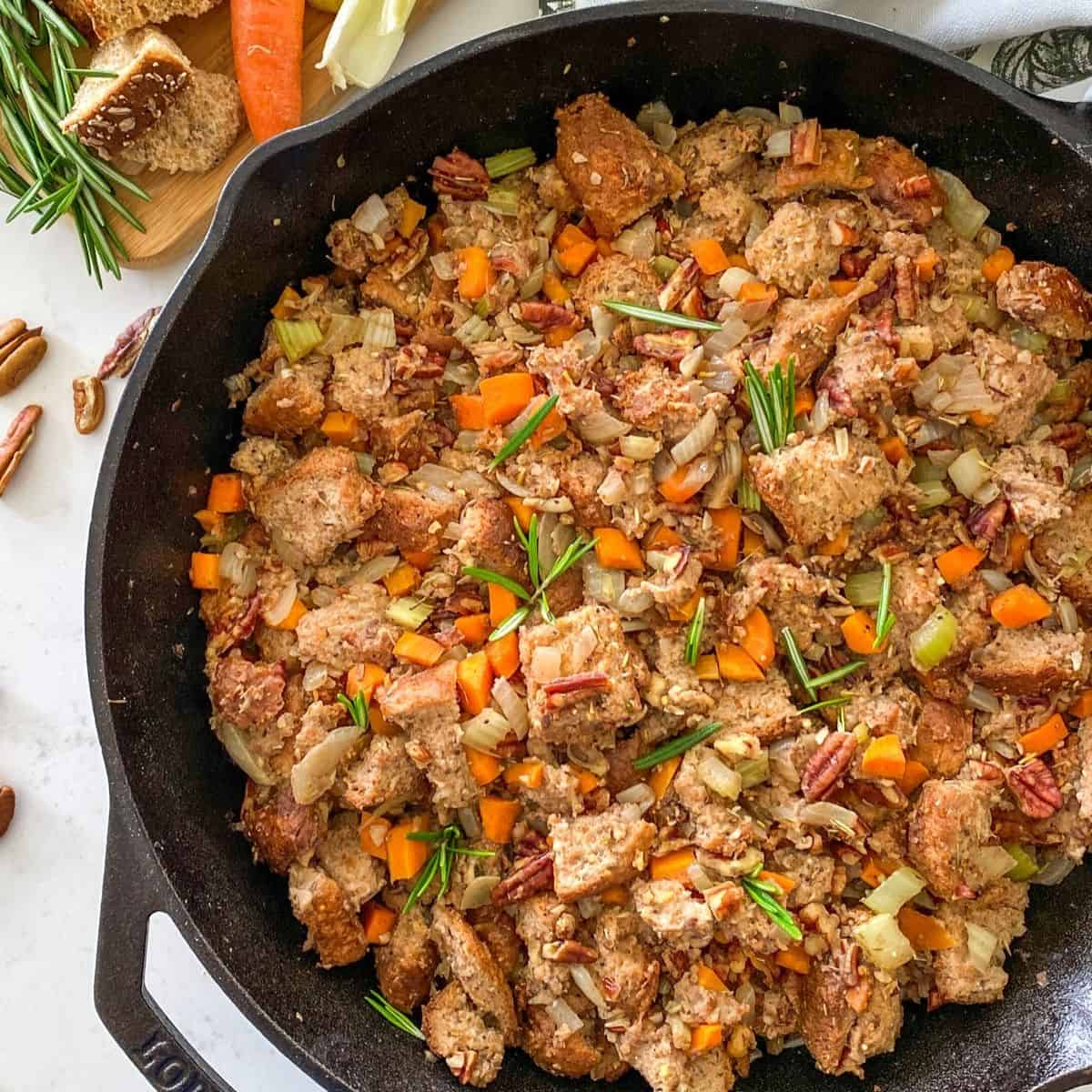Cast iron pan filled with bread, pecans, carrots, onion and rosemary garnish.