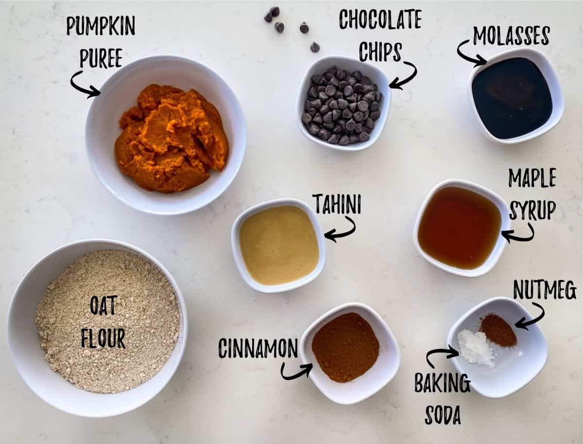 Ingredients required to make pumpkin chocolate chip cookies scattered in prep bowls on countertop.
