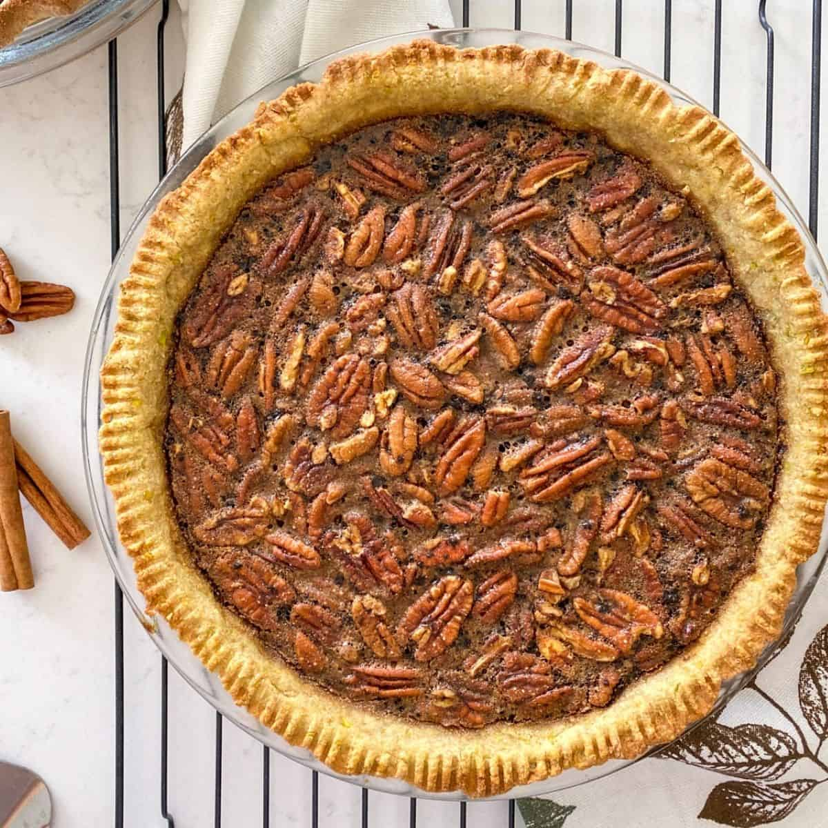 Pecan pie on cooling rack with cinnamon sticks and pecans beside it.