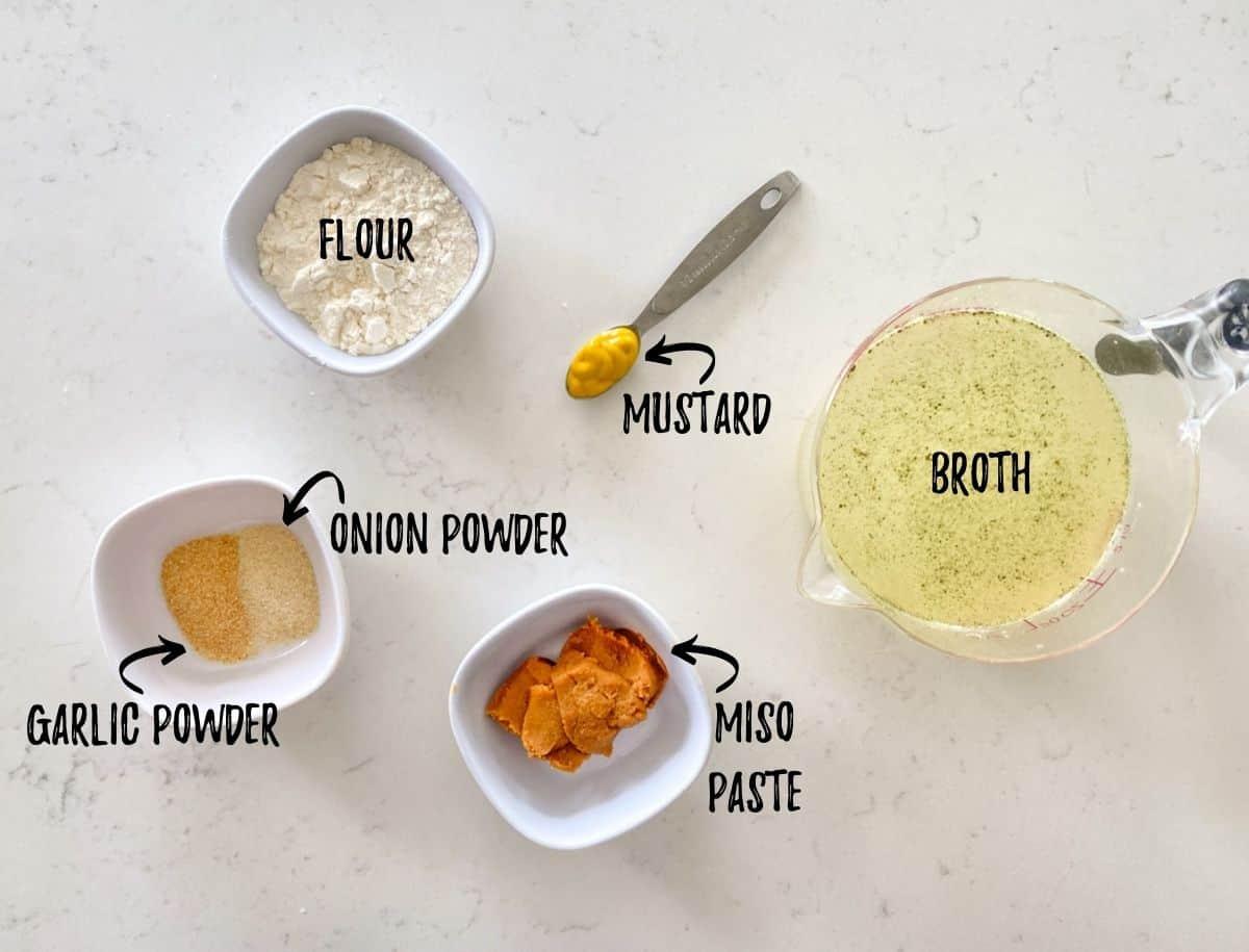 Ingredients needed to make miso gravy in prep bowls on kitchen counter.